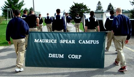 "Boys with drums marching, holding a sign reading, ""Maurice Spear Campus Drum Corp."""